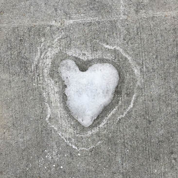 Snow on concrete in the shape of a heart