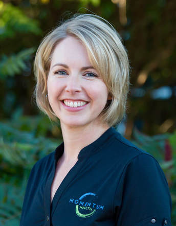 Photo of Naturopathic Doctor Erica Volk standing beside brick wall and smiling